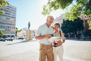 Senior couple using a city map