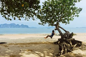 Girl swinging at a beautiful tropical beach in Thailand
