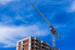Hoisting crane working on building