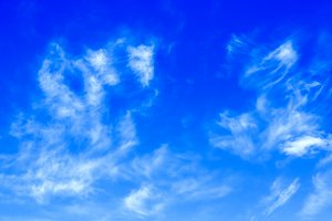 Clouds on clear blue sky background