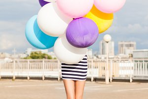 Beautiful sporty girl with balloons.