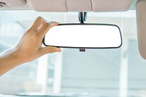 Hand adjusting rear view mirror
