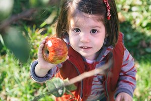 Little girl holding organic apple in her hand
