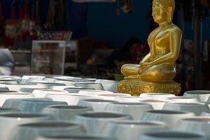 Cup of golden Buddha in Prayer