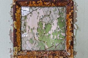 Rusty window in door of old hospital