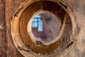 Face peering through door peephole