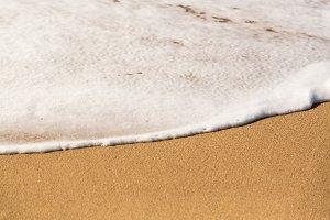 Ocean against sandy beach scene