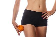 Slim figure woman holds an orange.