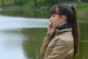 Young woman stands on the embankment of the river and talking on a cell phone. Girl speaking on smartphone outdoor in spring. Close-up
