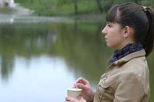 Beautiful young girl stands on the embankment of the river and drinking cup of takeaway coffee from disposable cup