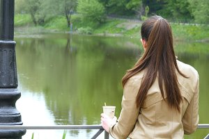 Back view of young girl drinking cup of takeaway coffee from disposable cup. Woman thoughtfully looks out over river and holding cup of tea to warm up