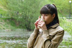 Beautiful young girl in the park drinking cup of takeaway coffee  from disposable cup. Portrait of attractive woman thoughtfully looks out over river and holding cup of tea  to warm up