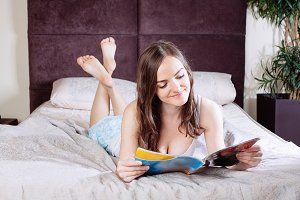 woman reading magazine at bedroom