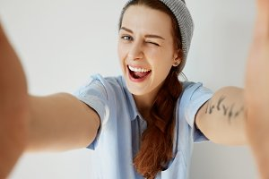 Wide-angle shot of funny young woman having fun with her friends during weekend. Portrait of stylish tattooed girl winking at the camera with mouth wide open. Human face expressions and emotions