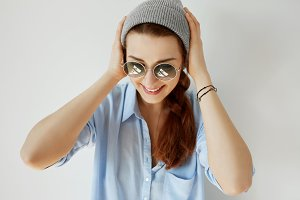 Portrait of redhead hipster girl wearing casual T-shirt, stylish gray cap and trendy sunglasses smiling and holding her head. Beautiful woman posing on white wall. Human face expressions and emotions