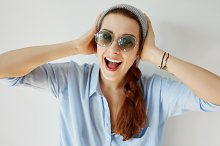 Close up portrait of happy redhead young woman in gray cap looking in excitement holding her head with both hands with mouth wide open, isolated against white wall. Excited and surprised female
