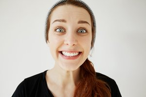 Surprised Caucasian woman with red hair and blue eyes looking and smiling at the camera in astonishment and shock. Funny hipster girl having fun posing with happy expression against studio wall.