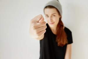 Selective focus, film effect. Close up of young stylish girl showing fig sign at the camera. Hipster female wearing gray cap and black T-shirt having fun making fig gesture posing isolated indoor.