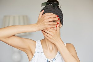 Portrait of young hipster woman peeping at the camera through her fingers. Picture of embarrassed female looking through her hands covering her face isolated against home interior background