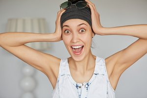 Close up portrait of happy beautiful young woman in gray headband looking excited holding her head with both hands with mouth wide open, isolated against white wall. Shocked and surprised female
