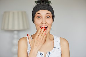 Portrait of excited young female saying yes to her boyfriend's proposal, can't believe she is going to get married soon, covering her open mouth in amazement. Human face expressions and emotions