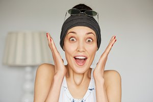 Portrait of young brunette woman wearing headband and sunglasses on her head screaming with excitement and joy.  Headshot of happy excited female with winning expression on her face, mouth wide open