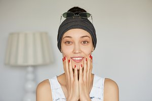 Close up shot of beautiful happy girl with perfect skin looking and smiling at the camera with pleased expression, holding her face with both hands posing against home interior background. Body language