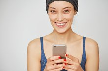 Beautiful smiling casual woman holding smartphone, looking and smiling at the camera isolated against white studio wall background with copy space for your text or advertising content. Film effect