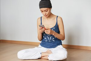 Young female ordering food delivery online using electronic device after practicing yoga at home. Hipster girl sitting with crossed legs on the floor messaging with her friends via social networks