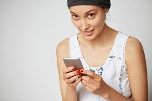 Cropped shot of young female freelancer looking and smiling at the camera while using free high-speed Internet connection sitting in cafe waiting for her boyfriend. Modern technology concept