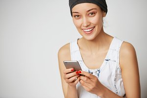 Technology and connection concept. Happy young woman looking and smiling at the camera while enjoying high-speed Internet connection posing against white blank copy space wall for your advertisement