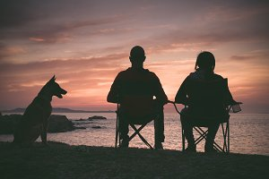 Couple and dog looking at sunset