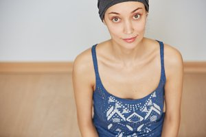 Overhead isolated view of beautiful young woman with healthy skin wearing casual clothes, looking at the camera while sitting on the floor after doing physical exercises indoor. Selective focus