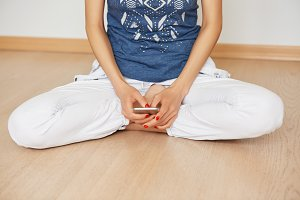 Cropped shot of woman sitting in lotus pose on the wooden floor while typing text message on mobile phone. Young mother resting while her children asleep communicating with friends via social networks