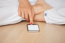 Close up view of female hands pointing on mobile phone blank screen with copy space for your advertisement. Young woman using high-speed Internet connection while sitting on the wooden floor at home