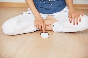 Cropped portrait of student girl wearing white pants, using cell phone with blank copy space screen for your text or promotional content while sitting on the wooden floor after practicing yoga.