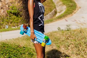 Beautiful black girl with skateboard