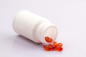 Orange capsules on white background