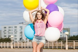 Pretty girl with bunch of balloons.