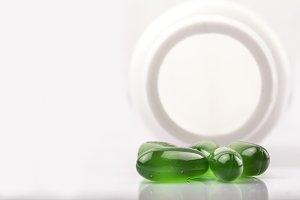 Green capsules in white bottle