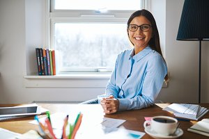 Self employed woman wearing glasses at desk