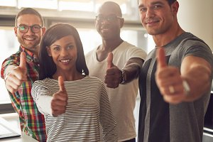 Four small business owners with thumbs up