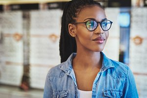 Grinning young woman in eyeglasses looking over