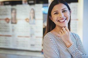 Single beautiful smiling woman in eye wear store