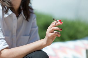 Woman rolling tobacco and smoking