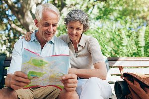 Happy mature couple using city map
