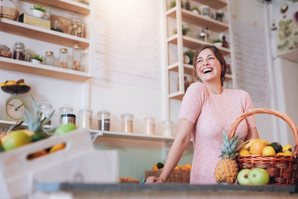 Smiling woman standing at a juice b…