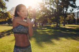 Athletic woman stretching arms