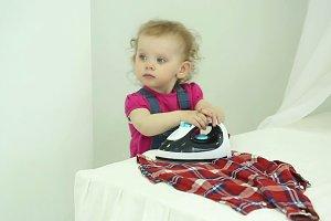 Little girl ironed shirt.