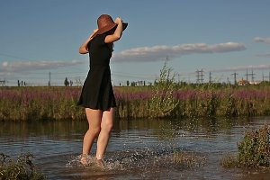 Girl splashing on river bank